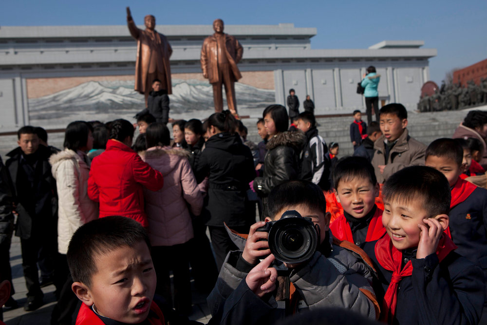 Description of . North Korean children play with the camera of a visiting Associated Press photographer as people gather in front of bronze statues of the late leaders Kim Il Sung and Kim Jong Il in Pyongyang, North Korea on Saturday, Feb. 16, 2013. North Koreans turned out to commemorate what would have been the 71th birthday of Kim Jong Il who died on Dec. 17, 2011. (AP Photo/David Guttenfelder)