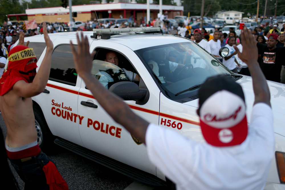 ". Demonstrators protesting the shooting death of Michael Brown yell at the police officers in a vehicle as some chant, ""Hands Up, Don\'t Shoot\"", as they make their voices heard on August 17, 2014 in Ferguson, Missouri. Violent outbreaks have taken place in Ferguson since the shooting death of Michael Brown by a Ferguson police officer on August 9th.  (Photo by Joe Raedle/Getty Images)"