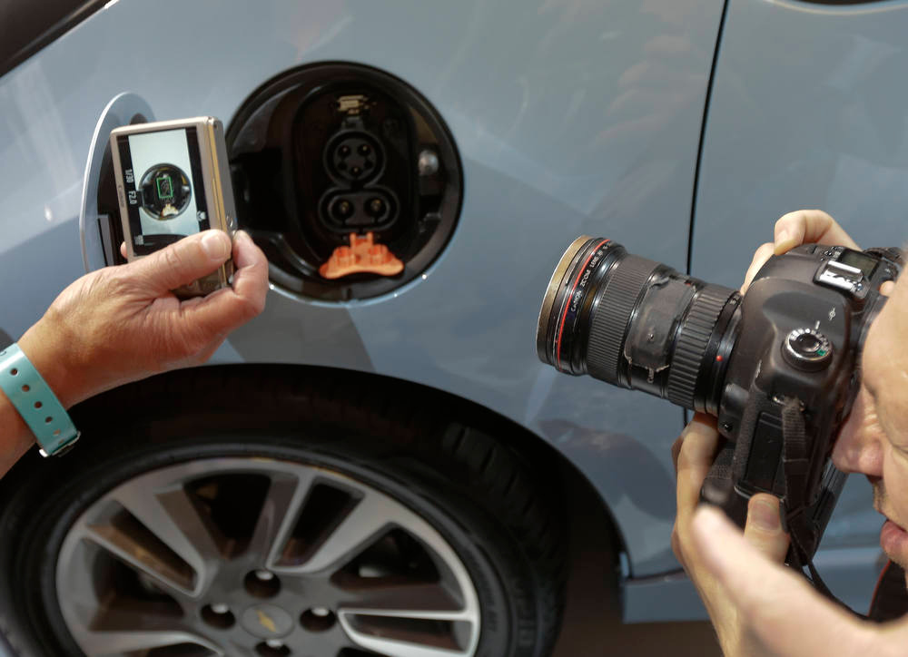 Description of . Members of the media look photograph the charging port on the Chevy Spark EV during it's world debut at the LA Auto Show in Los Angeles, Wednesday, Nov. 28, 2012. (AP Photo/Chris Carlson)