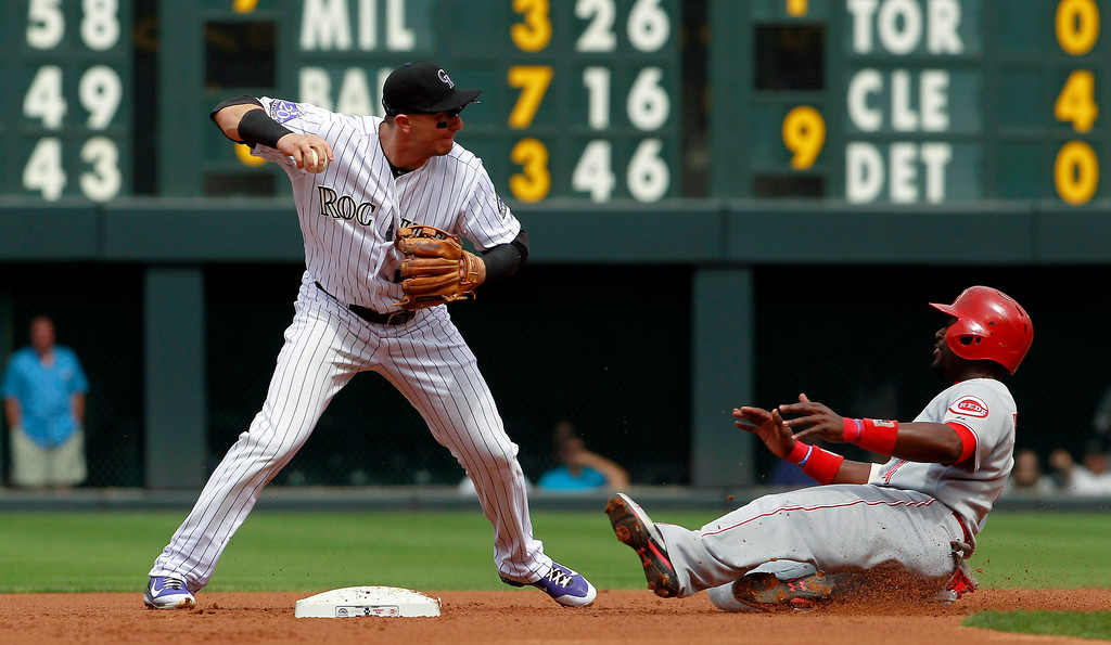 . Colorado Rockies shortstop Troy Tulowitzki, left, throws to first base after forcing out Cincinnati Reds\' Brandon Phillips, right, at second base on the front end of a double play hit into by Joey Votto in the first inning of a baseball game in Denver, Sunday, Sept. 1, 2013. (AP Photo/David Zalubowski)