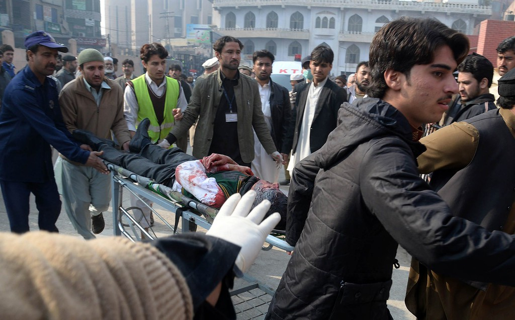 . Pakistani men carry an injured student to a hospital following an attack by Taliban gunmen on a school in Peshawar on December 16, 2014. At least 130 people were killed in a Taliban attack on an army-run school in northwest Pakistan, officials said.   AFP PHOTO/ A  Majeed/AFP/Getty Images