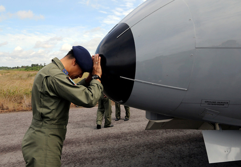 . A crew member of Indonesian Navy CN-235 airplane prays prior to the start of a search operation for the missing AirAsia flight 8501 at the airport in Pangkal Pinang, Bangka Island, Indonesia, Tuesday, Dec. 30, 2014. Six bloated bodies and debris seen floating in Indonesian waters Tuesday painful ended the mystery of AirAsia Flight 8501, which crashed into the Java Sea and was lost to searchers for more than two days. (AP Photo/Tatan Syuflana)