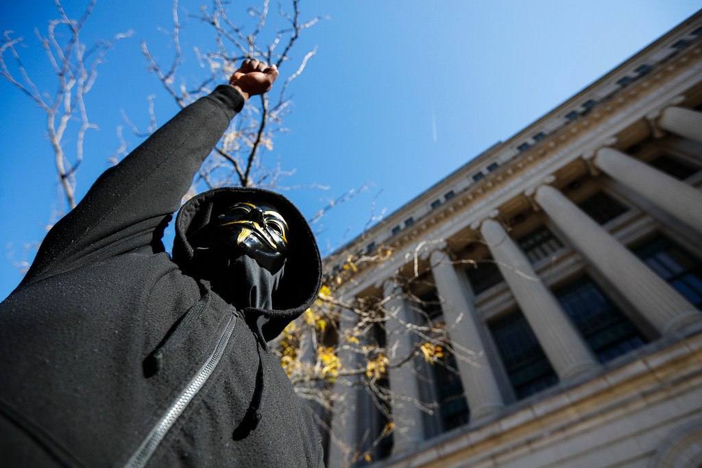 . A protestor raises his fist outside the Hamilton County Courthouse after a mistrial is declared due to a hung jury in the murder trial against Ray Tensing, Saturday, Nov. 12, 2016, in Cincinnati. Tensing, a white former University of Cincinnati police officer, was charged with murder in the shooting of Sam DuBose, an unarmed black motorist, while on duty during a routine traffic stop on July 19, 2015. (AP Photo/John Minchillo)