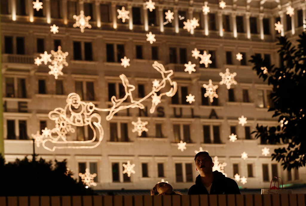 . A couple look at the illuminated decoration to celebrate the festival season during Christmas eve in Hong Kong,Tuesday, Dec. 24, 2013. (AP Photo/Kin Cheung)