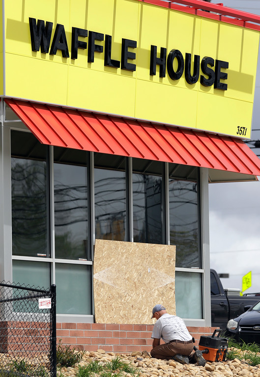 . A worker vacuums up shattered glass outside a Waffle House restaurant Monday, April 23, 2018, in Nashville, Tenn. A suspect police have identified as Travis Reinking shot and killed at least four people at the restaurant Sunday. (AP Photo/Mark Humphrey)
