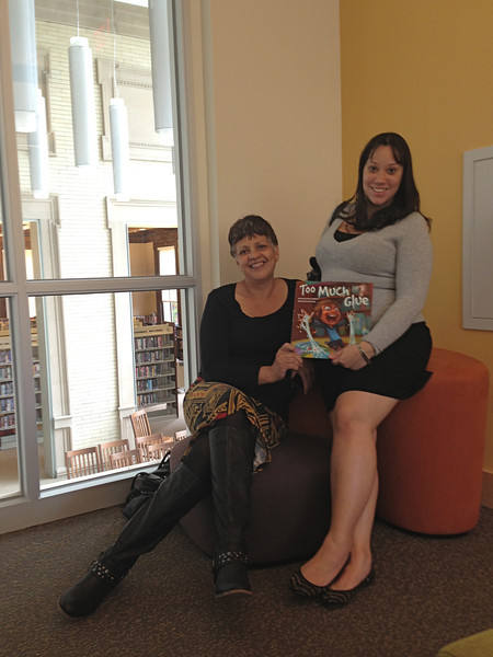 Maritza and Yajaira holding a copy of HPL staff member Jason Lefebvre's newly-published book.