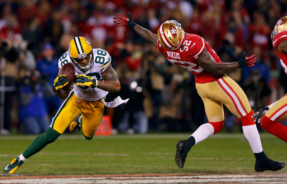 Description of . Green Bay Packers Jermichael Finley (L) makes a catch next to San Francisco 49ers Patrick Willis (R) in the second quarter during their NFL NFC Divisional playoff football game in San Francisco, California, January 12, 2013.  REUTERS/Mike Blake