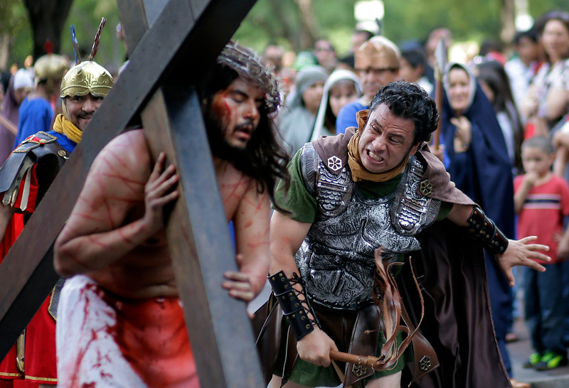 . Jose Nina, left, is whipped as he carries a cross playing the part of Jesus in a passion play and procession, Friday, April 18, 2014, in downtown San Antonio. More than 100 actors take part in the Good Friday tradition. (AP Photo/Eric Gay)