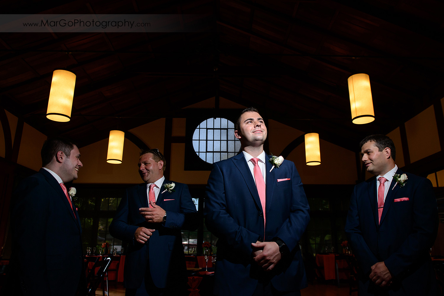 portrait of groom in blue suit and pink tie with groomsmen in background at Saratoga Foothill Club