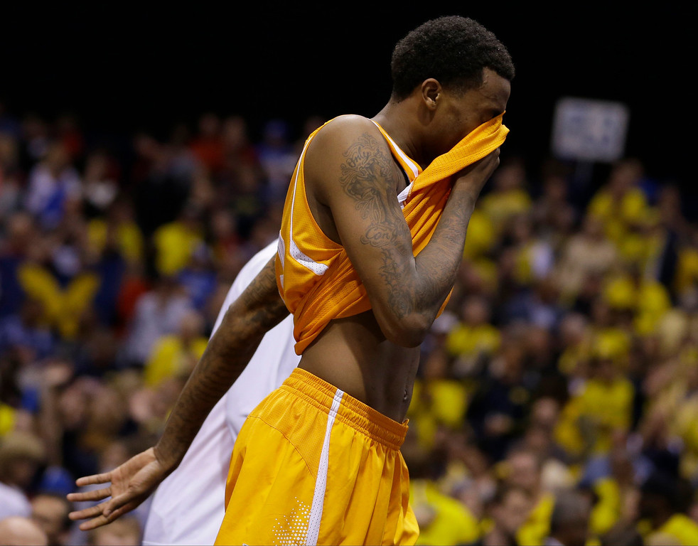 . Tennessee\'s Jordan McRae wipes his face as he walks off the court after an NCAA Midwest Regional semifinal college basketball tournament game against the Michigan Friday, March 28, 2014, in Indianapolis. Michigan won 73-71.(AP Photo/Michael Conroy)