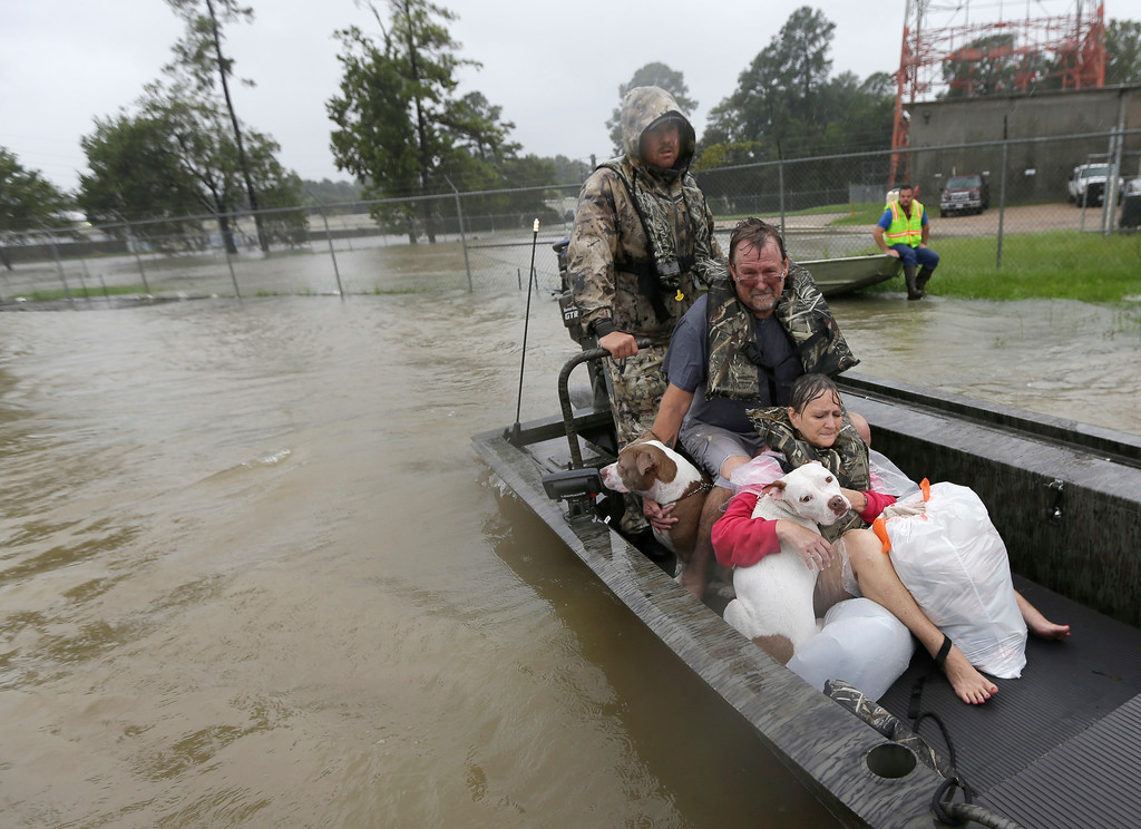 . John and Cathy Cservek hold their dogs Lacy and Iggy while being rescued from their home as floodwaters from Tropical Storm Harvey rise Monday, Aug. 28, 2017, in Spring, Texas. (AP Photo/David J. Phillip)