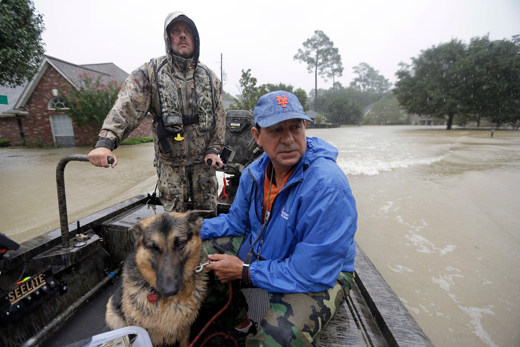 . Joe Garcia, right, and his dog Heidi ride in Murphy Fire Department\'s Todd Herrington\'s boat after being rescued from his flooded home as floodwaters from Tropical Storm Harvey rise Monday, Aug. 28, 2017, in Spring, Texas. (AP Photo/David J. Phillip)