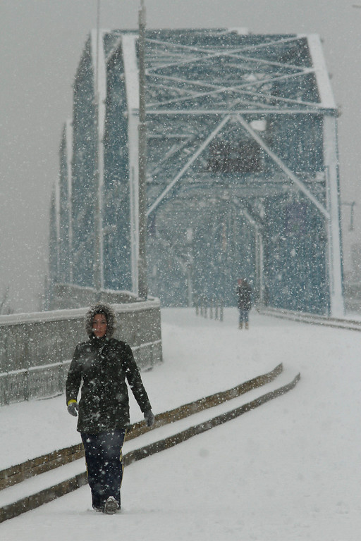 . Ashley Cuticchia walks across the Walnut Street Bridge as snow accumulates on Wednesday, Feb. 12, 2014 in Chattanooga, Tenn. The bridge is a pedestrian bridge that spans the Tennessee River. Slushy highways and streets were mostly desolate and ice encased trees and sent them crashing into power lines, knocking out electricity to a wide swath of the South as the winter-weary region was hit with its second winter storm in two weeks. (AP Photo/Chattanooga Times Free Press, Dan Henry)