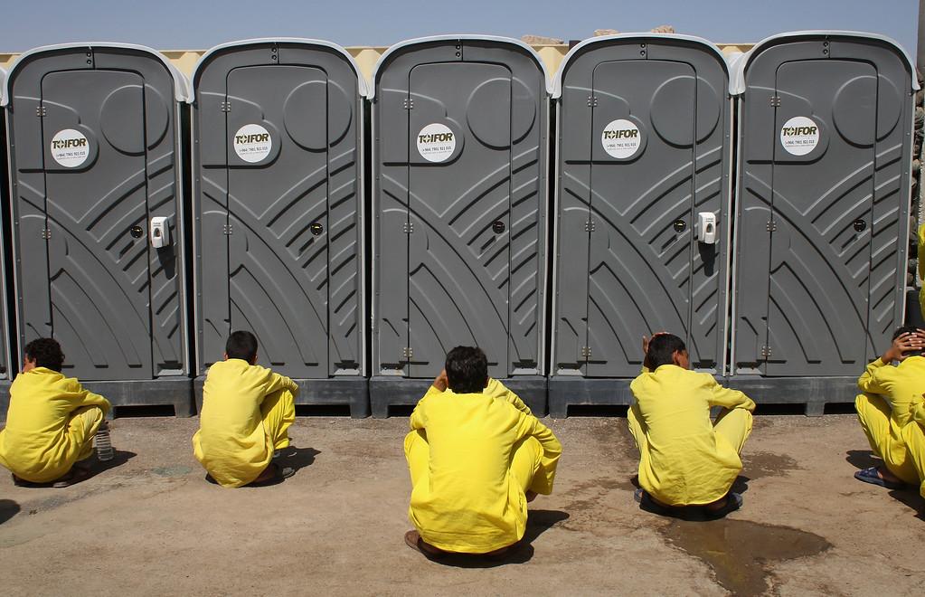""". Juvenile detainees wait for their turn outside portable bathrooms at the \""""House of Wisdom\"""" school operated by the U.S. military near the Camp Cropper detention center September 19, 2007 in Baghdad Iraq. More than 800 juvenile detainees were in American custody at the center. Most were captured during this year\'s American troop \""""surge\"""" in Baghdad. They attend six classes -  Arabic, Science, Math, History, Civics and English every three days. Many of the detainees, ages 12-17 years old, were captured while planting roadside bombs or IEDs targeting U.S. forces, according to military officials.  (Photo by John Moore/Getty Images)"""