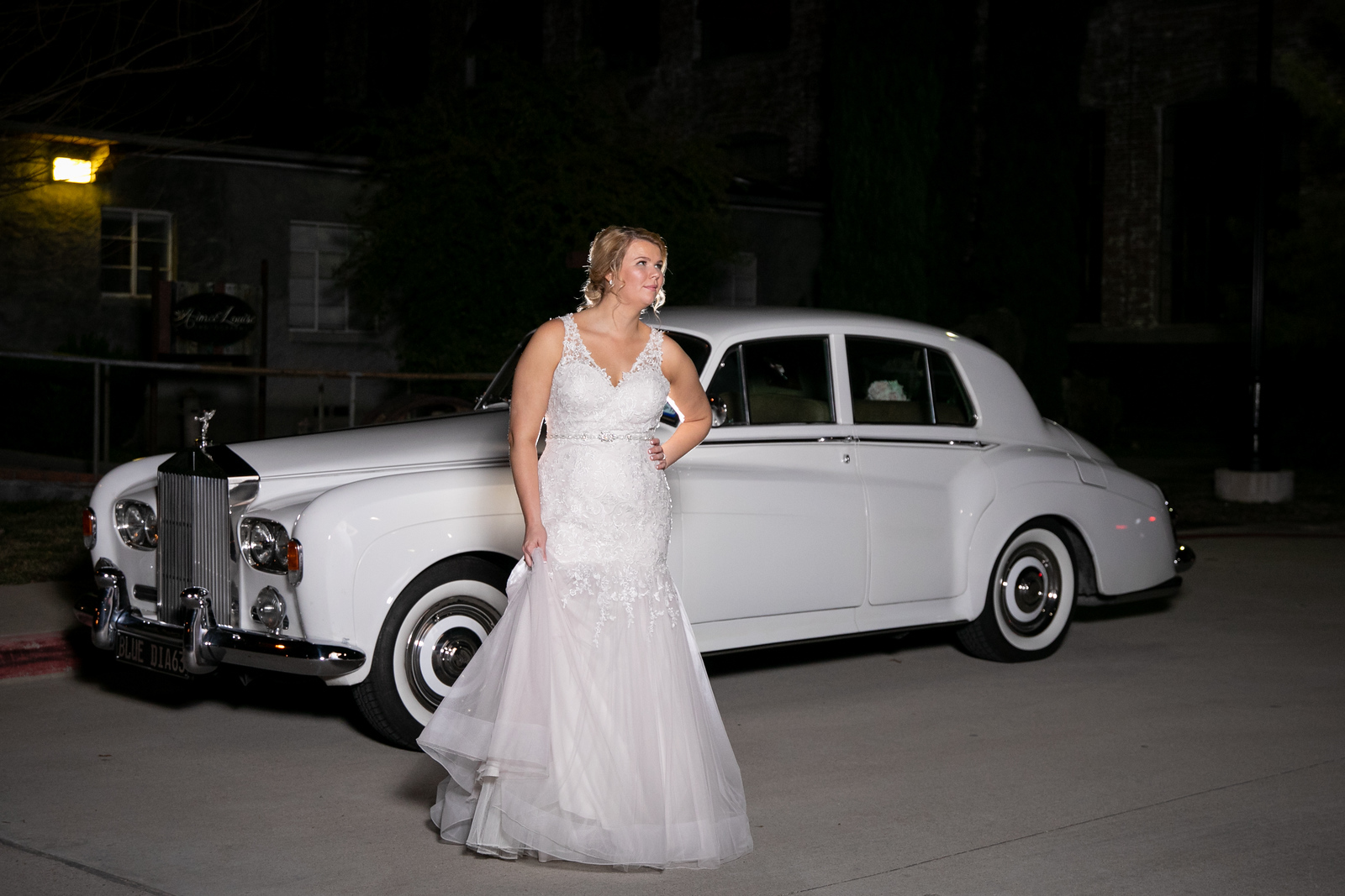 bride standing in front of a classic car outside her wedding venue on her wedding night