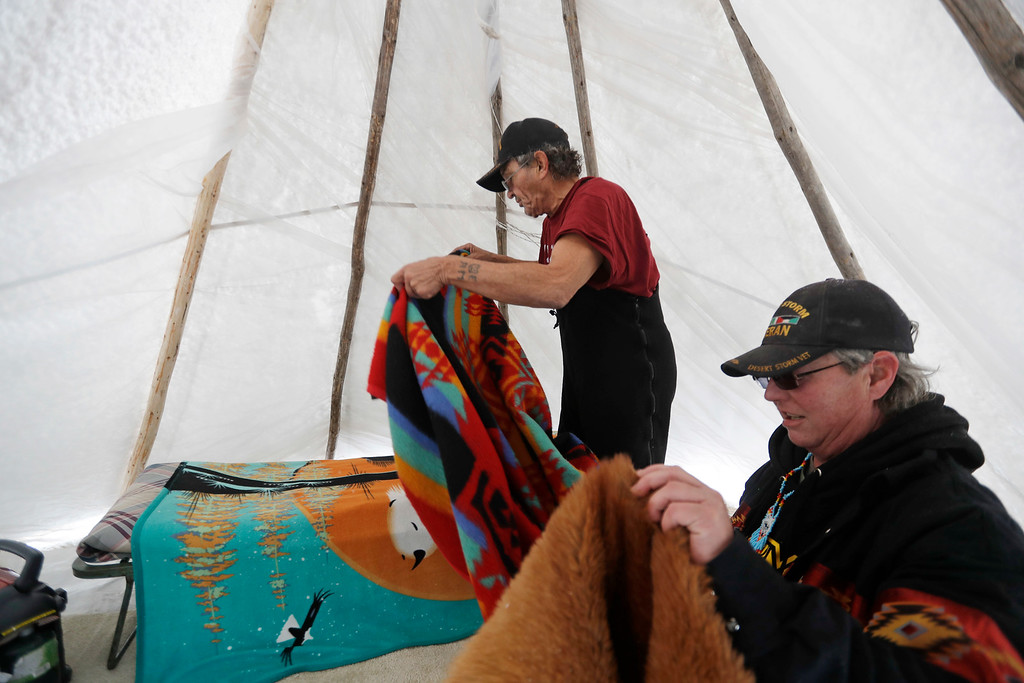 . Vietnam veteran and a Salish Metis Native American from Wyoming, Allen Coomsta Matt, left, gets help from Army veteran Cathy Gillespsie, of Kansas, setting up his bed in his teepee at the Oceti Sakowin camp where people have gathered to protest the Dakota Access oil pipeline as snow begins to fall in Cannon Ball, N.D., Monday, Dec. 5, 2016. Many Dakota Access oil pipeline opponents who\'ve gathered for months in a camp in southern North Dakota are committed to staying despite wintry weather and demands that they leave. (AP Photo/David Goldman)