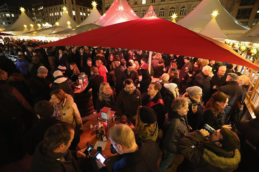 . Visitors crowd a mulled wine stand at the annual Christmas market at Gendarmenmarkt on its opening day on November 26, 2012 in Berlin, Germany. Christmas markets, with their stalls selling mulled wine (Gluehwein), Christmas tree decorations and other delights, are an integral part of German Christmas tradition, and many of them opened across Germany today.  (Photo by Sean Gallup/Getty Images)