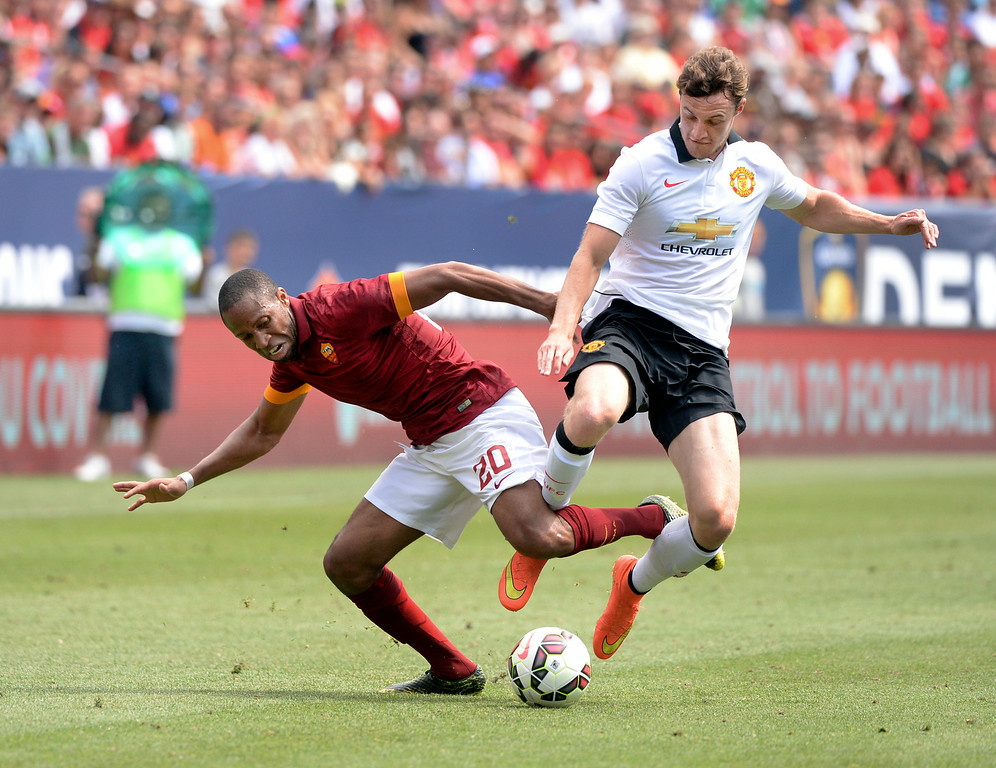 . Will Keane, right, got tangled up with AS Roma midfielder Seydou Keita, left, in the second half. Manchester United defeated AS Roma 3-2 in an exhibition soccer game at Sports Authority Field in Denver Saturday afternoon, July 27, 2014. Photo by Karl Gehring/The Denver Post