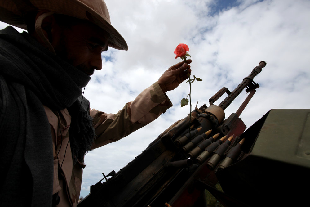 Description of . A member of Libya's security forces tucks a rose into an ammunition belt in Benghazi, Libya, Saturday, Feb. 16, 2013, a day ahead of the two year anniversary of the uprising that ousted Moammar Gadhafi.  (AP Photo/Mohammad Hannon)