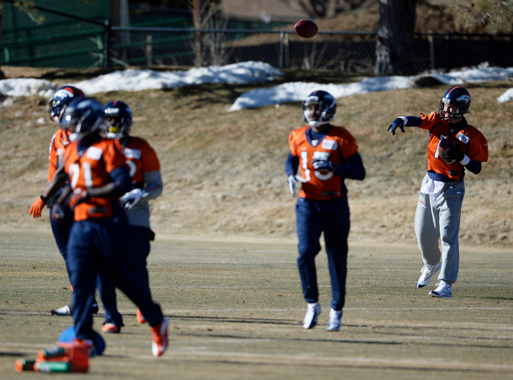 . Denver Broncos QB, Peyton Manning, right, throws a few warm-up passes  during practice at Dove Valley Saturday morning, January 25, 2014. (Photo By Andy Cross / The Denver Post)