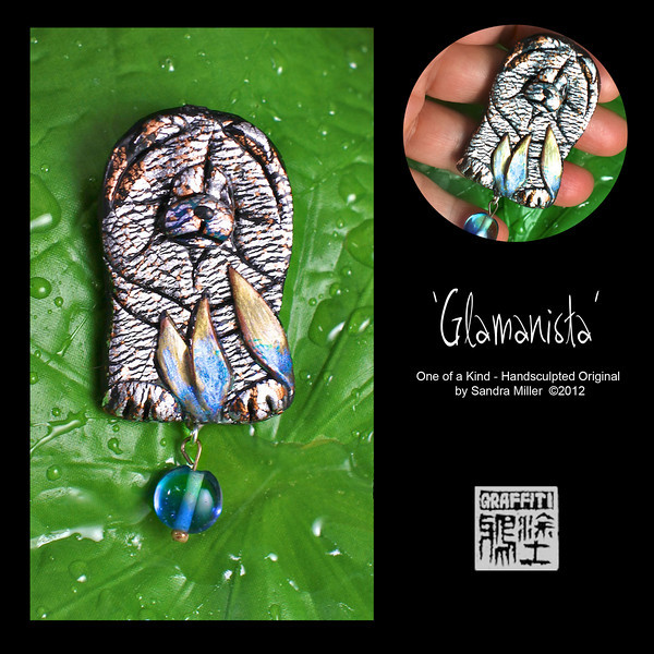 """GLAMANISTA- Brooch Pin  GLAMANISTA is such a great size brooch, and couldn't you see her worn with jeans or even that little black dress.   The chow is sculpted of polymer clay which first has been layered in iridescent finishes and metallic leaf. (See photo 4) The effect is almost like Raku glazing on Japanese porcelain. Breathtaking in person!!  Below her dangles a two tone hand made glass charm bead.  The crackle finish on this girl has such a textural quality.  It has been a long time since I have created some brooch pins and this year I have a handful to offer in the Trunk Show.   BROOCH MEASURES 2 1/2"""" X 1 1/2"""""""