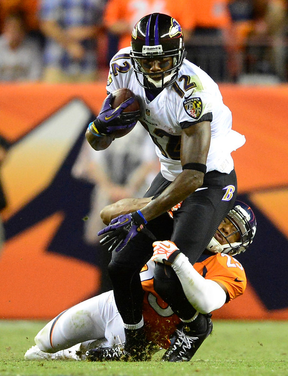 . Denver Broncos cornerback Chris Harris (25) tackles Baltimore Ravens wide receiver Jacoby Jones (12).  (Photo by AAron Ontiveroz/The Denver Post)