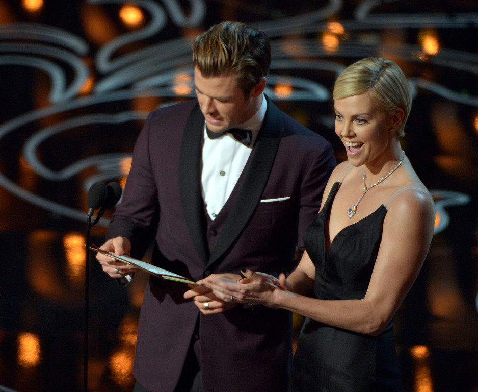 . Chris Hemsworth, left, and Charlize Theron present an award during the Oscars at the Dolby Theatre on Sunday, March 2, 2014, in Los Angeles.  (Photo by John Shearer/Invision/AP)