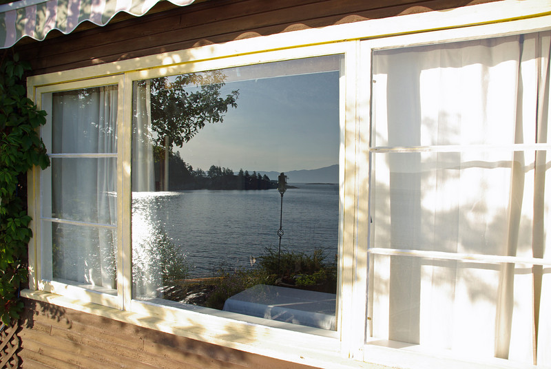 Looking into the living room from the sun deck, with a reflection of the view.