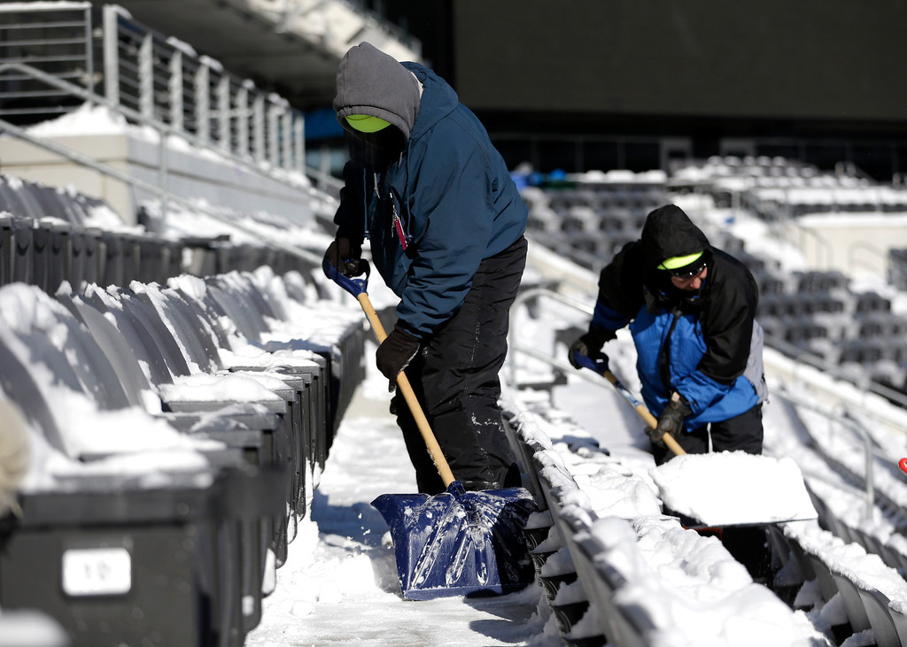 . Workers shovel snow off the seates at MetLife Stadium as crews removed snow ahead of Super Bowl XLVIII following a snow storm, Wednesday, Jan. 22, 2014, in East Rutherford, N.J.  (AP Photo/Julio Cortez)