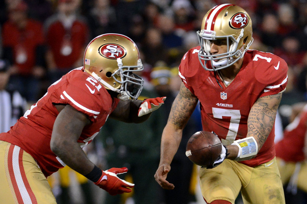 Description of . Quarterback Colin Kaepernick #7 of the San Francisco 49ers hands the ball to running back Frank Gore #21 against the Green Bay Packers during the NFC Divisional Playoff Game at Candlestick Park on January 12, 2013 in San Francisco, California.  (Photo by Harry How/Getty Images)