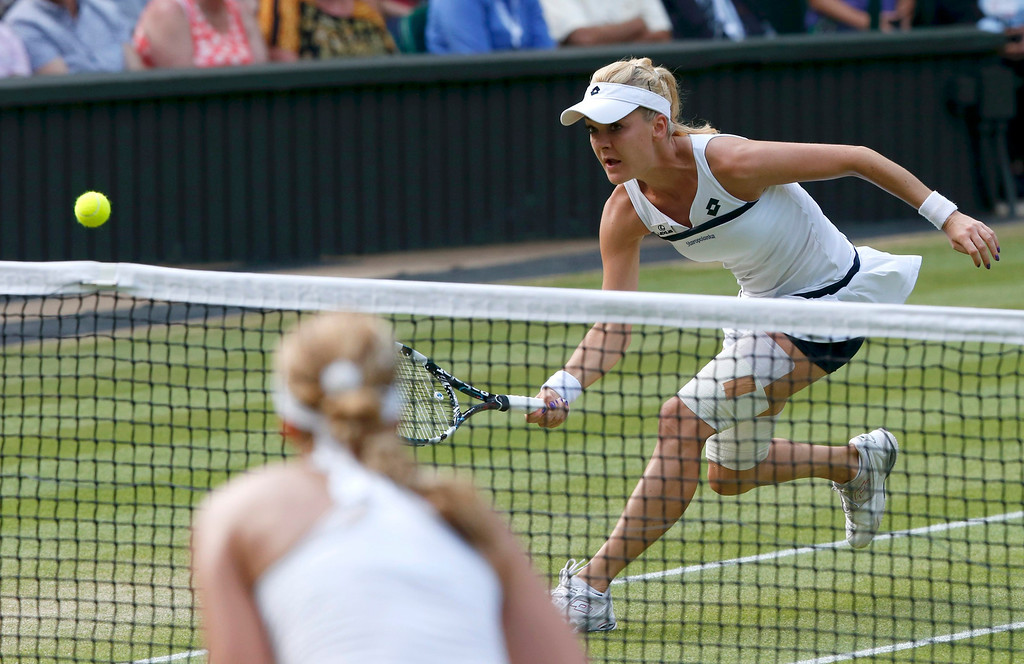 . Agnieszka Radwanska of Poland runs to hit a return to Sabine Lisicki of Germany during their women\'s semi-final tennis match at the Wimbledon Tennis Championships, in London July 4, 2013.          REUTERS/Suzanne Plunkett