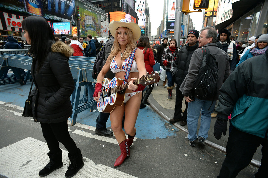 . The Naked Cowgirl walks up Broadway on December 31, 2013 at Times Square in New York. Cold temperatures are forecast as the crowd is expected to reach one million to watch the New Year ball to drop.   DON EMMERT/AFP/Getty Images