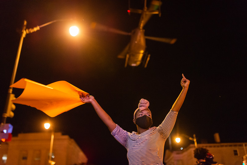 A demonstrator holds up an obscene gesture, as a helicopter flies low over protesters in an effort to disperse the crowd in Washington, DC on June 1, 2020.