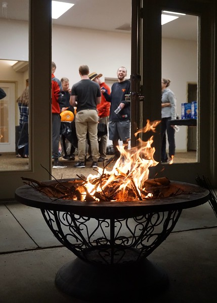 Students carve pumpkins while the fire burns outside, waiting for students to roast marshmallows.