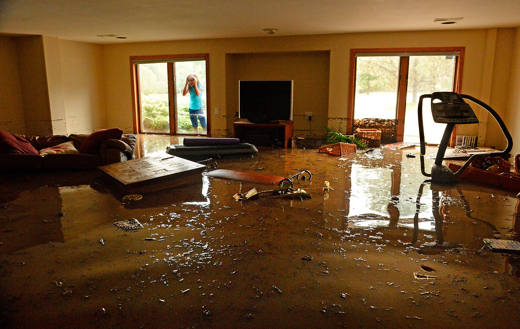 . Casey Roy, 9, peers through a basement window at her family\'s home on Premier Place in north Boulder. Floodwater rose to 3 feet in the basement on Sept. 12, 2013.