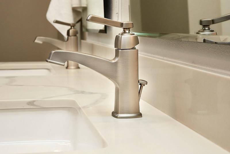 Modern bathroom faucets on clean marble sink.