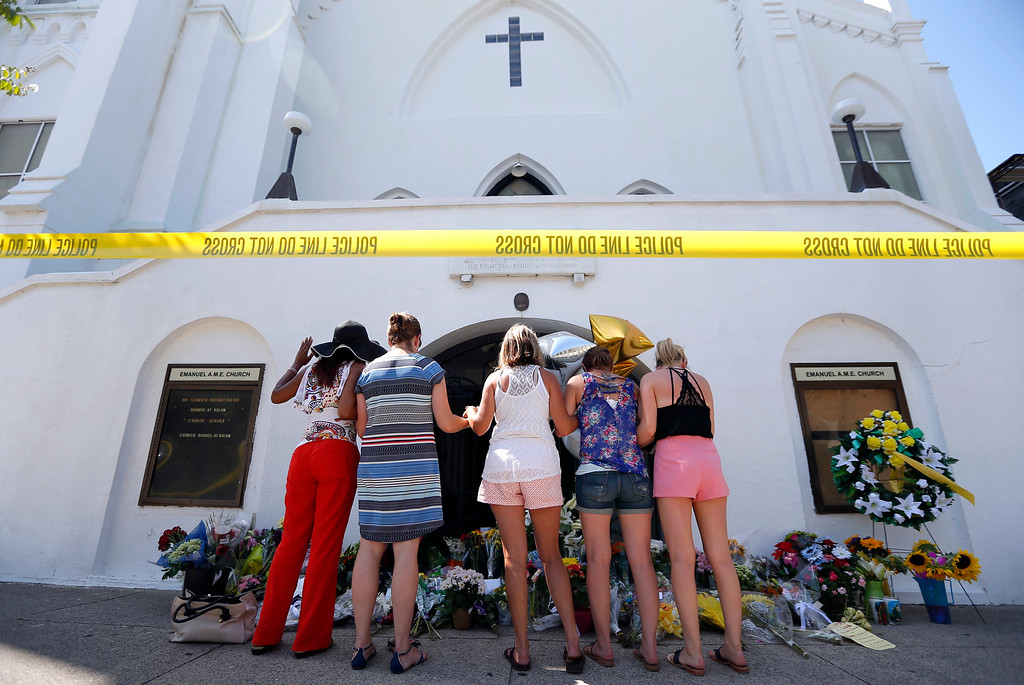 . A group of women pray together at a make-shift memorial on the sidewalk in front of the Emanuel AME Church, Thursday, June 18, 2015 in Charleston, S.C.  Dylann Storm Roof, 21, was arrested Thursday in the slayings of several people, including the pastor at a prayer meeting inside the historic black church.  (AP Photo/Stephen B. Morton)