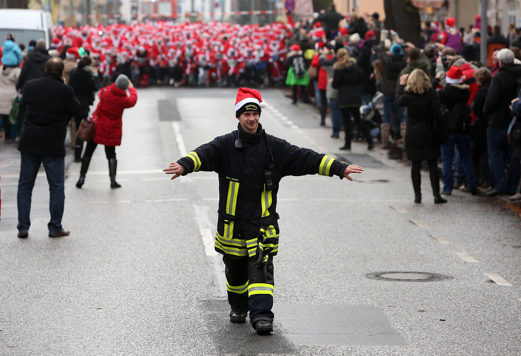. A fireman clears the road for the 5th annual Michendorf Santa Run (Michendorfer Nikolauslauf) on December 8, 2013 in Michendorf, Germany. Over 900 people took part in this year\'s races, which included one for children and one for adults.  (Photo by Adam Berry/Getty Images)