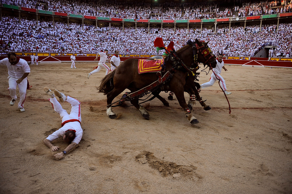 . An assistant falls as mules run around the bull ring, at the end of bullfight, at the San Fermin fiestas, in Pamplona northern Spain on Thursday, July 11, 2013. (AP Photo/Alvaro Barrientos)