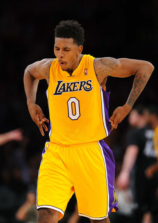 . The Lakers\' Nick Young holsters his weapons after sinking a three-pointer in the fourth quarter against the Timberwolves, Friday, December 20, 2013, at Staples Center. (Photo by Michael Owen Baker/L.A. Daily News)