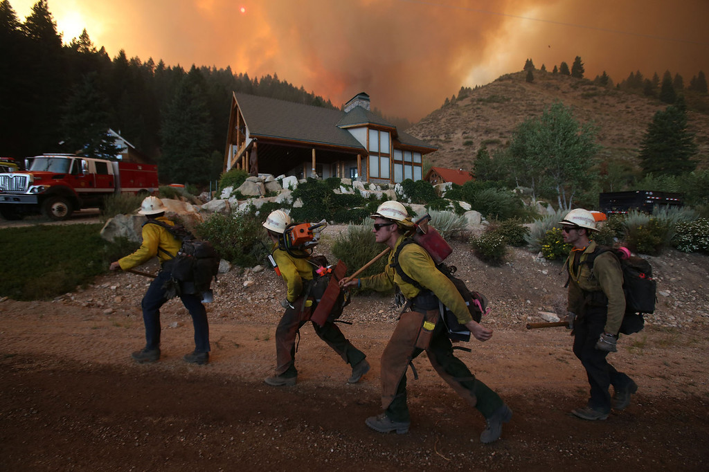 . Hundreds of firefighters, including the Ironwood Hotshots from Tucson, Ariz., gathered Sunday to battle the 80,300-acre Elk Fire Complex burning across Elmore County, Idaho, on Sunday, August 11, 2013.  The hotshots were protecting the home from the fire.(AP Photo/Times-News,Ashley Smith)