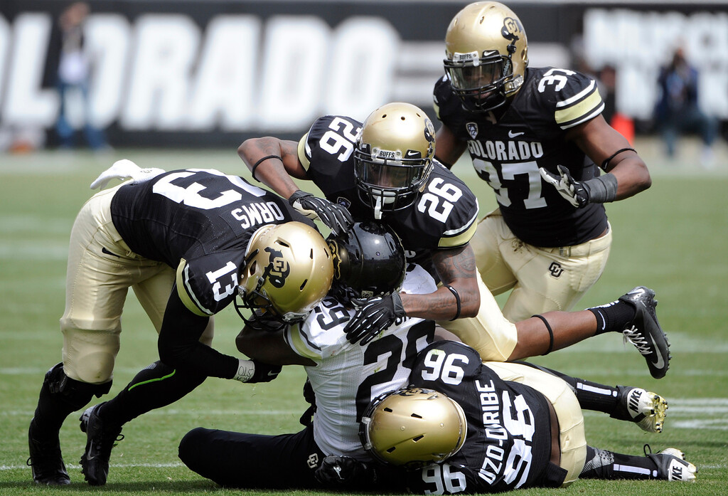 . BOULDER, CO.- APRIL13: Josh Ford is swallowed up by black team\'s defenders. The University of Colorado football team hosts its spring football game at Folsom Field under the direction of new head coach Mike Macintyre. (Photo By Kathryn Scott Osler/The Denver Post)