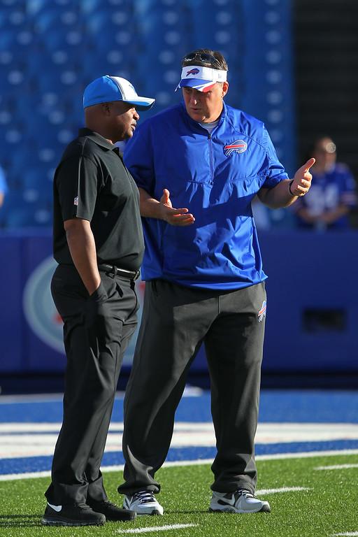 . Detroit Lions head coach Jim Caldwell, left, and Buffalo Bills head coach Doug Marrone talk before a preseason NFL football game, Thursday, Aug. 28, 2014, in Orchard Park, N.Y. (AP Photo/Bill Wippert)