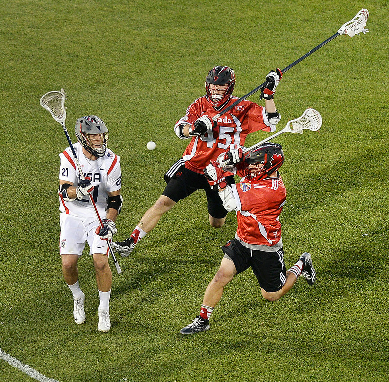. United States midfielder Ned Crotty (21) got rid of the ball under pressure in the second half. The United States defeated Canada 10-7 in the opening game of the FIL World Lacrosse Championships Thursday night, July 10, 2014.   Photo by Karl Gehring/The Denver Post