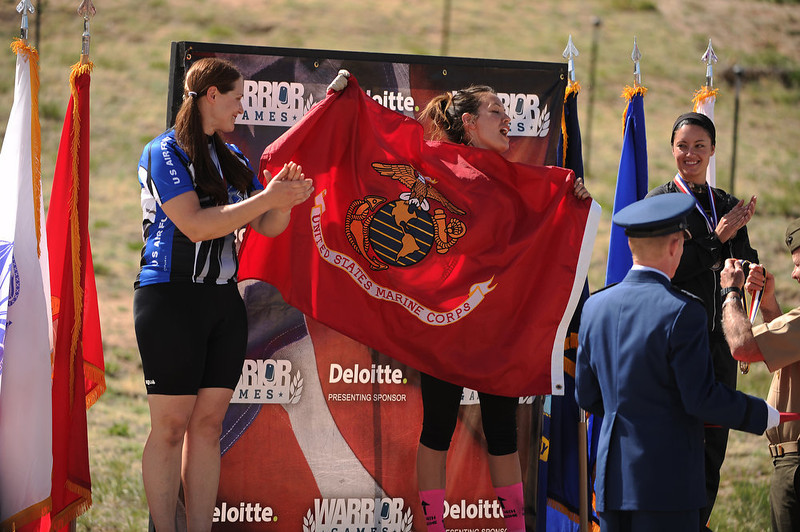 . Marine Lori Yrigoyen (recumbent bike) holds up the Marine flag and sings the Marines\' Hymn after taking home gold in the Women\'s 10K Handcycle & Recumbent Race.  The fourth annual Warrior Games cycling event took started and finished at Falcon Stadium on the grounds of the Air Force Academy in Colorado Springs, CO on May 12, 2013.  HRH Prince Harry was on hand to start the race as well as to hand out medals at the finish line.   A total of 260 wounded, ill and injured service members and veterans came to compete in the week long games.  Members of the Army, Marine Corps, Navy/Coast Guard/Air Force. Special Operations and the British Armed Forces all took part in the competition.  Other events included in the Warrior Games are shooting, sitting volleyball, track & field and wheelchair basketball.  (Photo by Helen H. Richardson/The Denver Post)