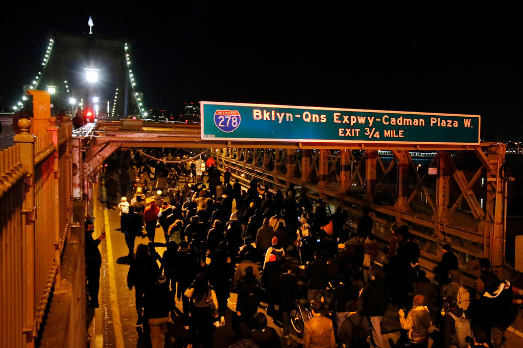 . A group of protesters rallying against a grand jury\'s decision not to indict the police officer involved in the death of Eric Garner marches across the eastbound traffic lanes of the Brooklyn Bridge in the early morning hours of Thursday, Dec. 4, 2014, in New York. (AP Photo/Jason DeCrow)