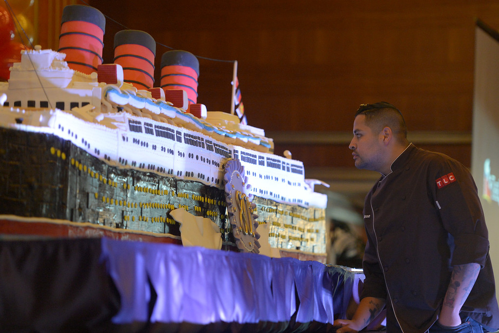 . Baker Jose Barajas looks over his 15-foot long, 600-pound cake built to replicate the Queen Mary to celebrate its 80th anniversary of her launching in Long Beach, CA on Friday, September 26, 2014. After some speeches and a short film, guests were able to sample a slice of the cake.  (Photo by Scott Varley, Daily Breeze)