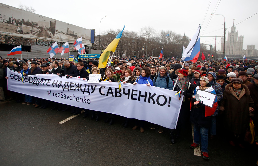 . People carry a banner reading \'freedom for Nadezhda Savchenko!\' as they march in memory of opposition leader Boris Nemtsov who was gunned down on Friday, Feb. 27, 2015 near the Kremlin, in Moscow, Russia, Sunday, March 1, 2015. Thousands converged Sunday in central Moscow to mourn veteran liberal politician Boris Nemtsov, whose killing on the streets of the capital has shaken Russiaís beleaguered opposition.   Female Ukrainian air force officer Nadezhda Savchenko was allegedly captured by Russian backed rebels in eastern Ukraine and taken to Russia on charges of involvement in the deaths of two Russian journalists, but she has been on hunger strike in a Moscow prison for more than two months, awaiting trial. She denies the accusations.  (AP Photo/Denis Tyrin)