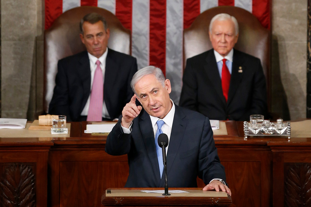 """. Israeli Prime Minister Benjamin Netanyahu gestures as  he speaks before a joint meeting of Congress on Capitol Hill in Washington, Tuesday, March 3, 2015. In a speech that stirred political intrigue in two countries, Netanyahu told Congress that negotiations underway between Iran and the U.S. would \""""all but guarantee\"""" that Tehran will get nuclear weapons, a step that the world must avoid at all costs. House Speaker John Boehner of Ohio, left, and Sen. Orrin Hatch, R-Utah, listen.  (AP Photo/Andrew Harnik)"""