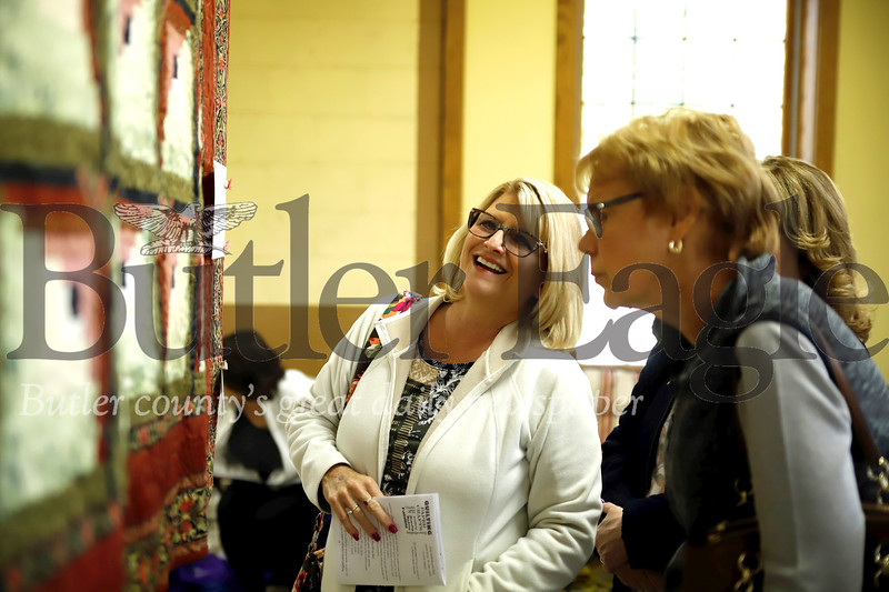 Terri Glover of Butler(left), looks at a quilt at the Quilt Show Saturday. Seb Foltz/Butler Eagle